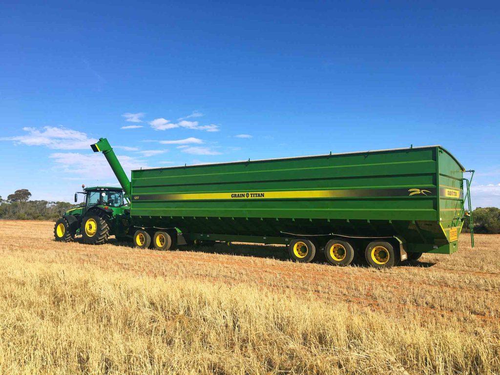 Field Bin in field of crops ready for harvesting green field bin green tractor