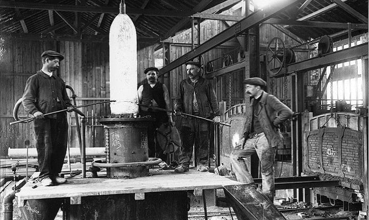 Men Standing Around Steel Fabarication During Olden Days